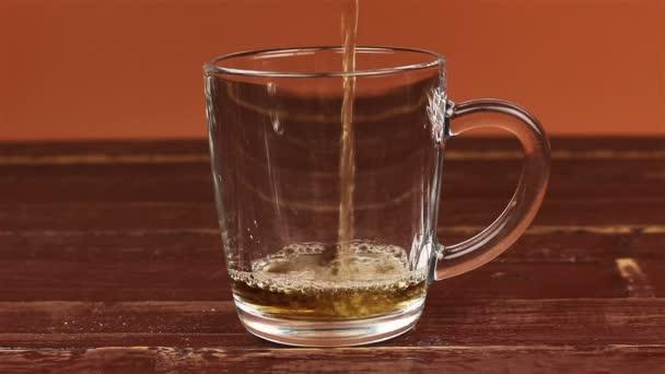 Tee wird in Glas Teetasse auf braunem Holztisch gegossen
