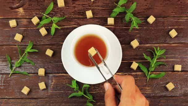 Cukr kostky do čaje sklo na stůl s čerstvé máty a hnědého cukru v kostkách na hnědý dřevěný stůl