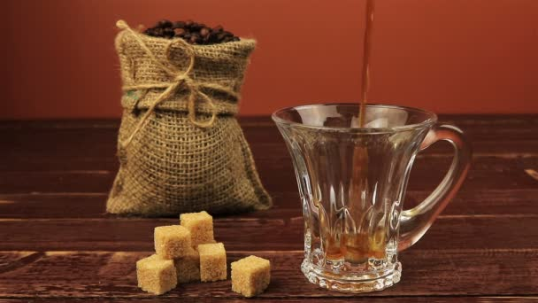 Pouring a cup of coffee on table located coffee beans in burlap bag, brown sugar cubes over brown wooden table