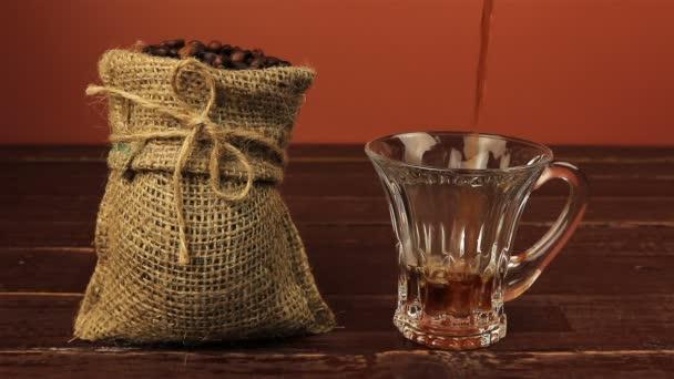 Öntés egy csésze kávé asztal található, szemes kávé zsákvászon zacskó mint barna fa tábla