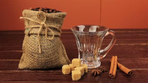 Nalil si šálek kávy na stole nachází kávová zrna v pytlovina pytel, hnědý cukr kostky a skořici hnědý dřevěný stůl