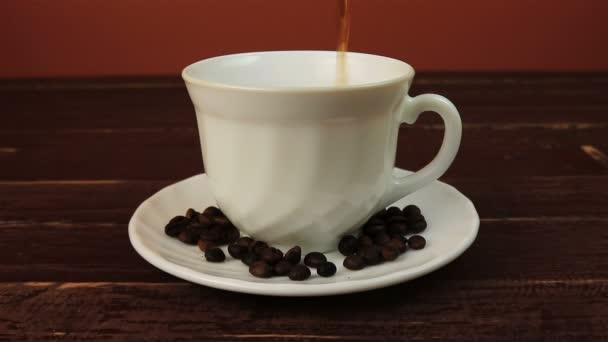 Nalil si šálek kávy zrnkové kávy na desce přes hnědý dřevěný stůl