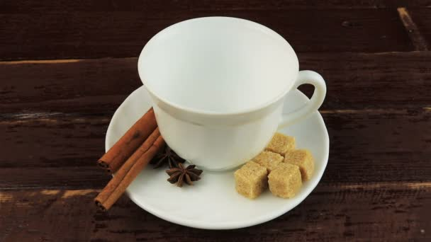 Öntés egy csésze kávé kávébab, a lemez, kockák barna cukor és fahéj botokkal barna fából készült asztal fölé