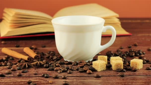 Nalil si šálek kávy na stole nachází kávová zrna, otevřená kniha, hnědý cukr kostky a tyčinky skořice hnědé dřevěný stůl