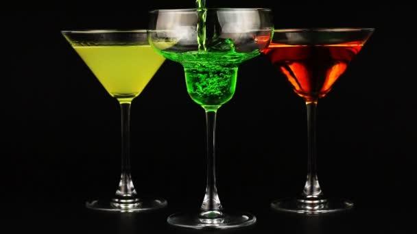 Gießen grünen Cocktail in Weinglas. drei Gläser verschiedener Cocktails auf schwarzem Hintergrund
