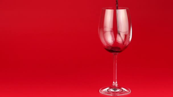 Red wine poured into glass on red background