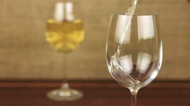 Bílé víno nalil do sklenice na dřevěný stůl