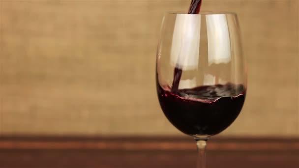 Červené víno nalil do sklenice na dřevěný stůl