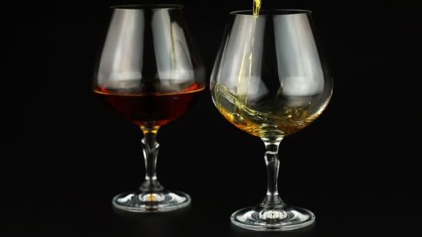 Brandy wird in ein Glas auf schwarzem Hintergrund gegossen