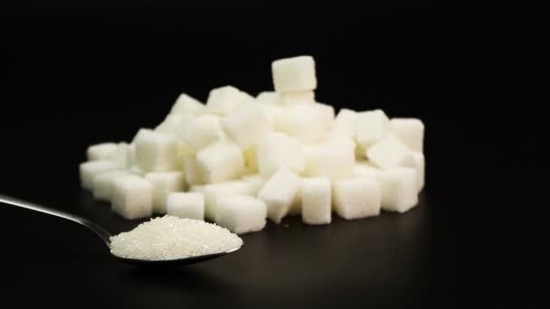Injekční stříkačka s obsahem inzulínu do hromady cukru vedle kostky cukru, diabetes koncept na černém pozadí