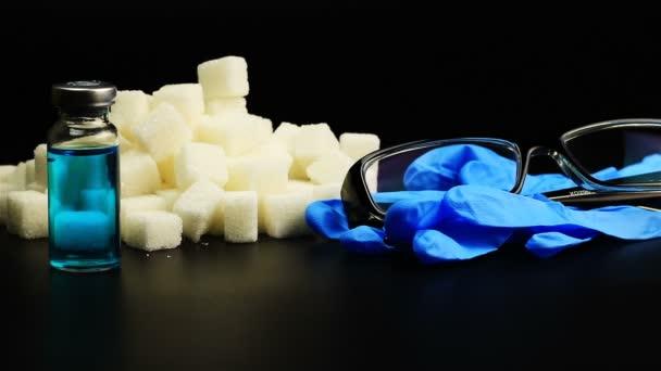 Injekční inzulín uvedení vedle kostky cukru, ampule, rukavice, brýle, diabetes koncept na černém pozadí
