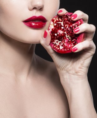 girl with red pomegranate in a hand