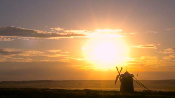 Starý větrný mlýn v poušti na pozadí zapadajícího slunce