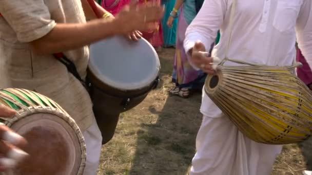 Krišna Festival. Muzikanti hrají bicí. Ženy v krásné indické šaty v pozadí.