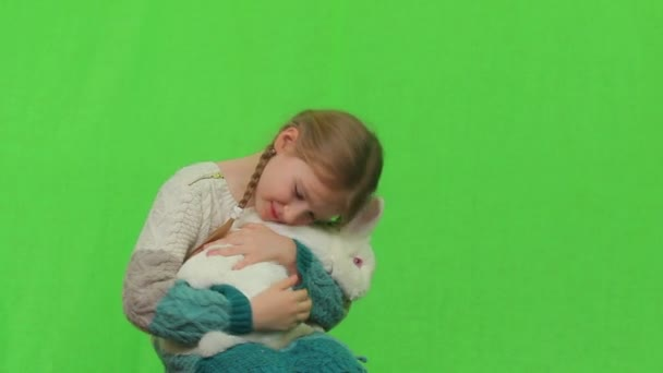 Girl with a white rabbit on a green screen