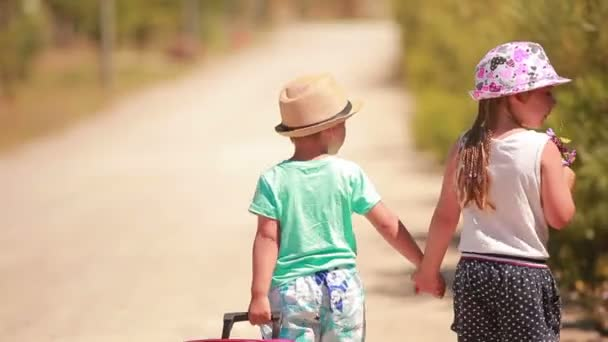 little girl and boy holding hands, go on on the road  with a case