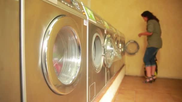 Frau wäscht Kleidung in die Waschmaschine in der Waschküche