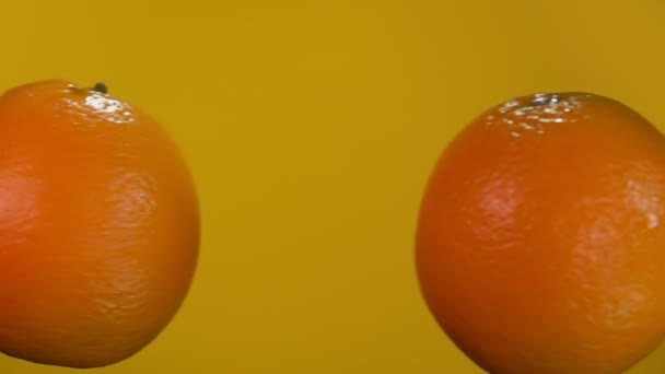 Two juicy oranges are flying towards each other rising drops of water