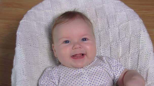 Egy kis vidám kék szemű baba nevet a kamerába.