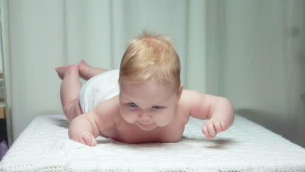 Malé roztomilé děťátko leží na břiše na bílé přikrývce