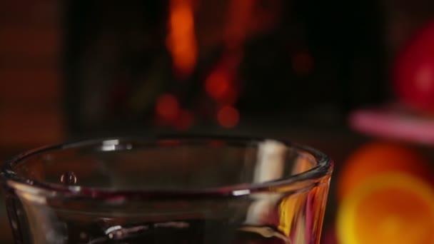 Nahaufnahme der Orangenscheibe, die in ein Glas mit Glühwein fällt
