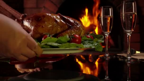 Plate with roasted chicken is placed on the table on the background of fire