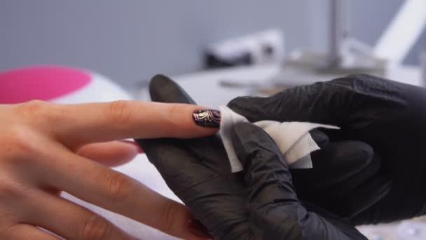 Der Maniküre-Meister in den schwarzen Handschuhen poliert nach der Maniküre den Nagel