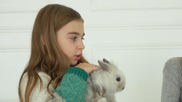 Langhaariges Mädchen im Strickkleid streichelt ein niedliches graues, flauschiges Kaninchen