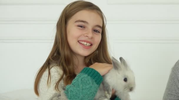 Happy long-haired girl is caressing a cute grey fluffy little rabbit