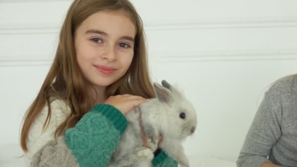 Happy smiling girl is caressing a cute grey fluffy little rabbit