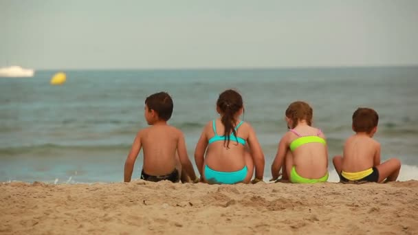 Children sit on the beach