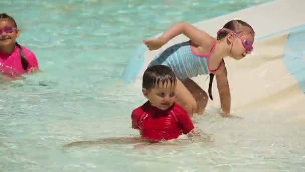 Děti jedou horská dráha v bazénu