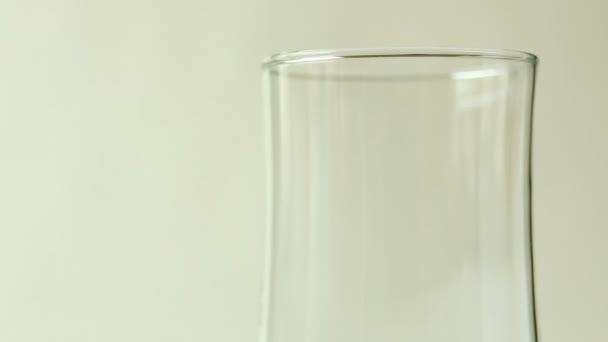Pivo se nalije do sklenice na bílém pozadí