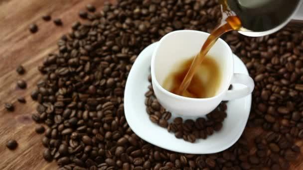 Kávu v šálku v kávová zrna