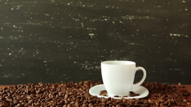 White coffee cup and beans on dark background