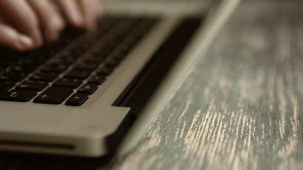 Hand eines Mannes, der am Laptop arbeitet und auf der Tastatur tippt. Rutsch nach links