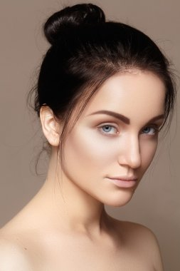 Beautiful young woman with clean face, shiny skin, fashion natural make-up, perfection eyebrows. Cute bun hairstyle. Spa portrait, naturel cosmetics, healthy fresh look
