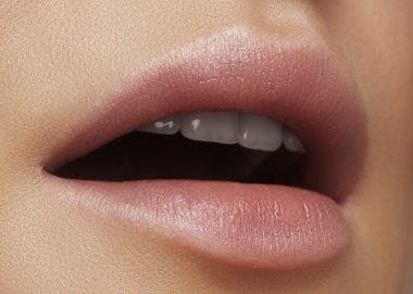 Close-up beautiful female lips with bright lipgloss makeup. Perfect clean skin, light fresh lip make-up. Beautiful spa macro shot with tender pink lip gloss. Spa and cosmetics