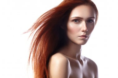 Beautiful ginger young woman with flying hair and naturel makeup. Beauty portrait of sexy model with straight red hair. Long soft shiny hairstyle. Close-up studio shot o fashion look redhead girl