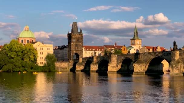 Scénický pohled na Staroměstskou přístavní architekturu a Karlův most přes Vltavu v Praze. Pražský kultovní Karlův most a Staroměstská mostecká věž při západu slunce.