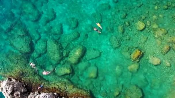 Letecký pohled na mladý pár, jak šnorchluje nad korálovým útesem a sahá hlouběji do křišťálově čisté vody, Rhodos, Řecko. Vzdušný letoun pohled na pár šnorchlování plavání v křišťálově čisté vodě.