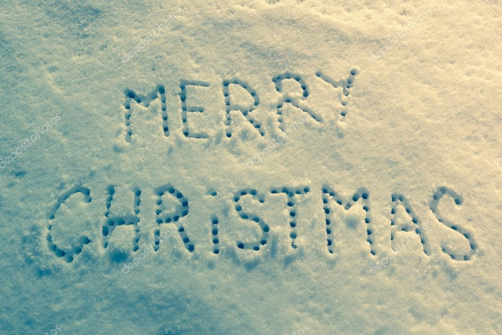 Written words Merry christmas on a snow field