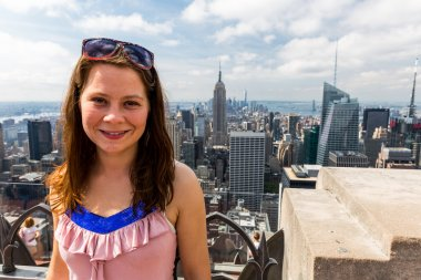 Girl taking selfies with view to Uptown Manhattan