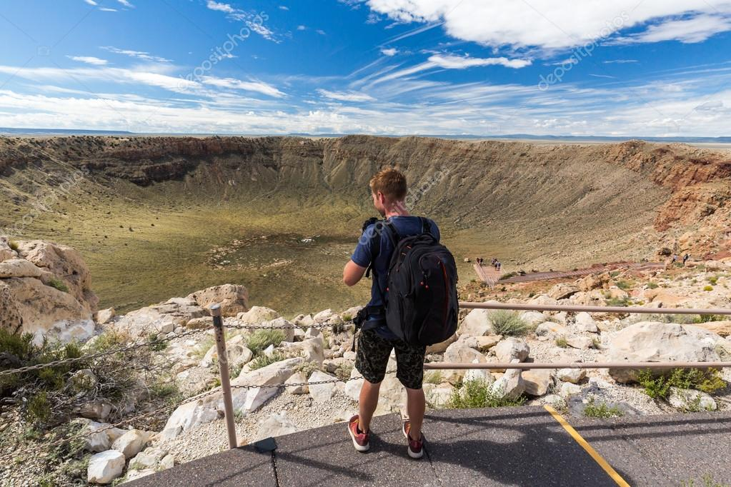 Man taking photos with view of the Meteor Crater, Flagstaff