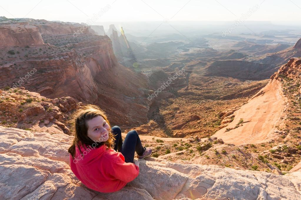 Girl sitting at the Mesa Arch at sunrise