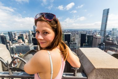 Girl taking selfie with view to Uptown Manhattan