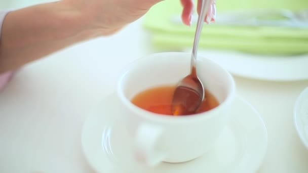 Woman mixing tea with spoon