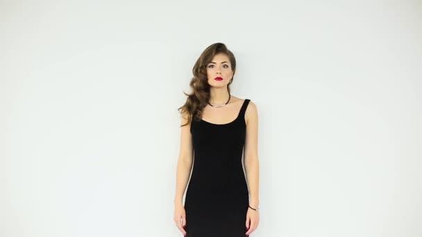 Krásná dívka v černých šatech na bílém pozadí
