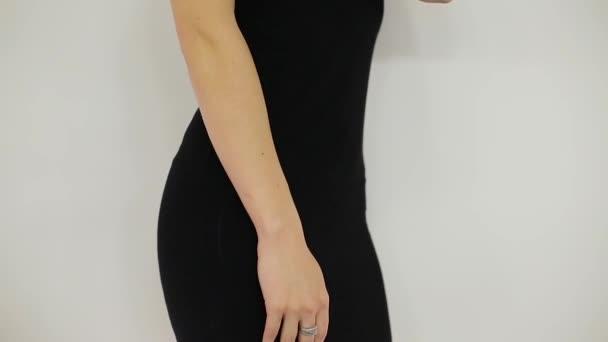 Mädchen streicheln eine schöne Taille im schwarzen Kleid