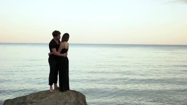 Pár fekete ruhát ölelni a szikla a tengerparton
